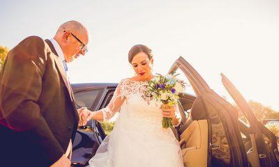 Padrino de boda y novia saliendo del coche de novios